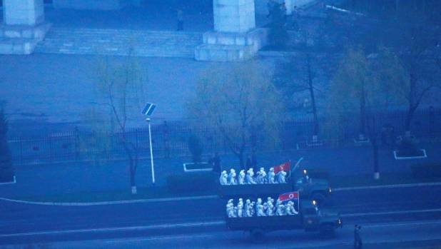 Military trucks carry soldiers through central Pyongyang before sunset as the capital preparers for a parade marking ...