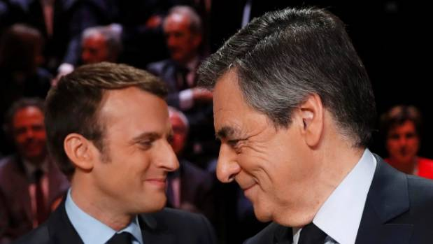 Francois Fillon, right, said campaigning should not be suspended. Emmanuel Macron, left, said it was important not to ...
