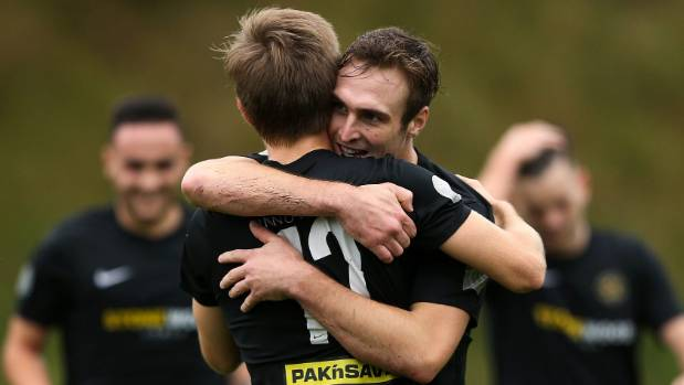Team Wellington's Ben Harris (facing) congratulates team-mate Andy Bevin on his goal on Sunday.