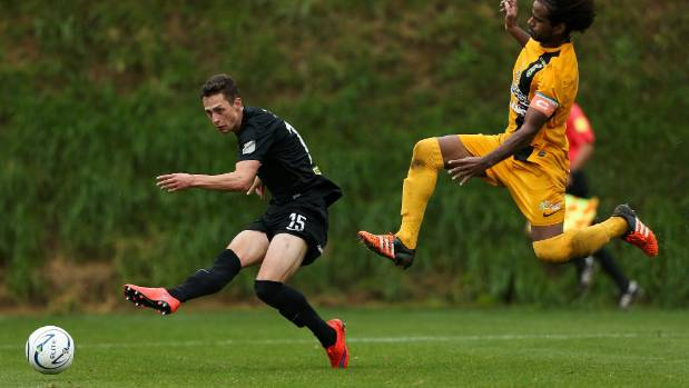Team Wellington's Joel Stevens scores his second goal on Sunday as AS Magenta's Jeremie Dokunengo flies in with a wild ...