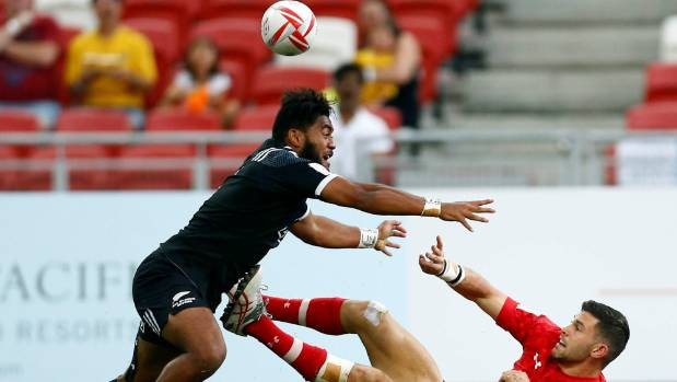 Canada's Justin Douglas passes after a tackle from New Zealand's Vilimoni Koroi.