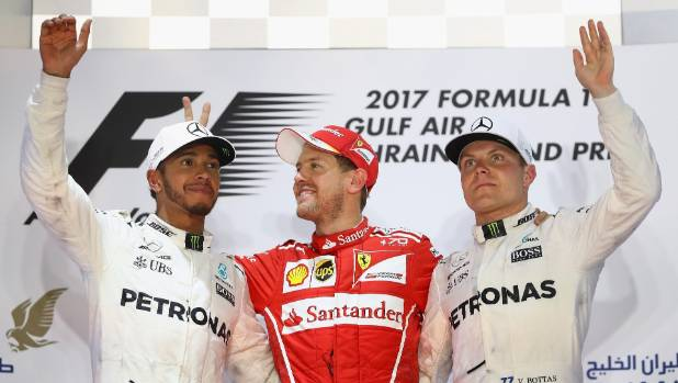 Top three finishers in Bahrain: Sebastian Vettel of Germany and Ferrari (centre), Lewis Hamilton of Great Britain (left) ...