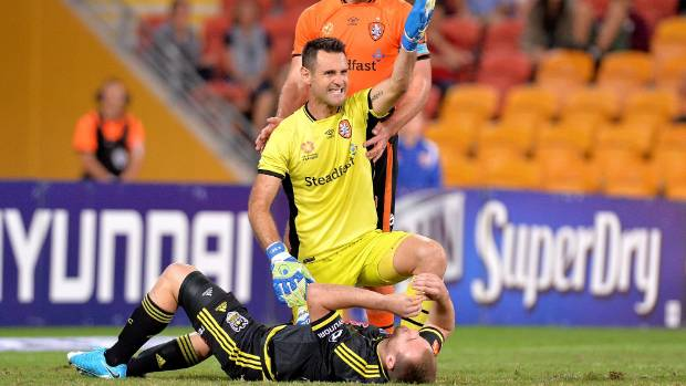 Brisbane Roar goalkeeper Michael Theo calls for the physio after colliding with Wellington Phoenix striker Hamish Watson.