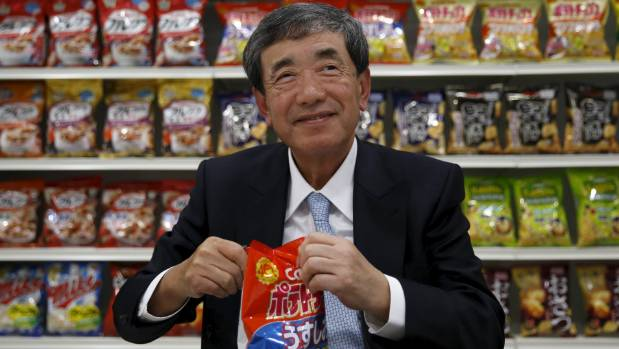 Akira Matsumoto, chairman and chief executive of Calbee, opens a pack of the company's potato chips in better times, 2016.