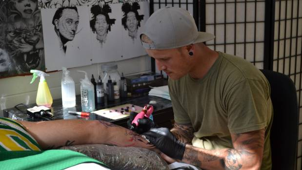 Sam Clayton tattooing a client's forearm.