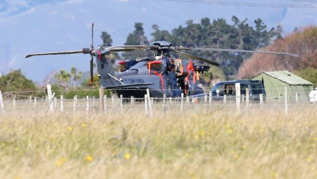 Defence force crews carry out repairs to the helicopter on Tuesday.