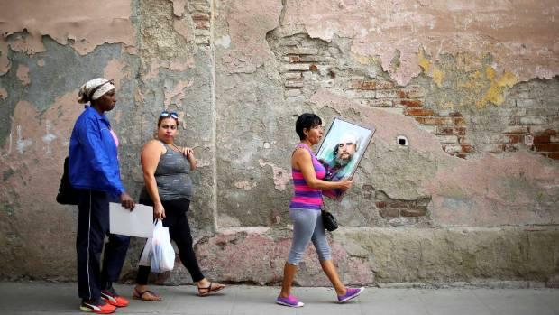 A woman carries a portrait of Cuba's late President Fidel Castro in Santa Clara.
