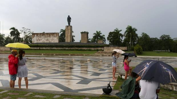 "Spanish tourists take pictures of a statue of late revolutionary hero Ernesto ""Che"" Guevara as Cubans connect to the ..."