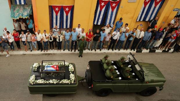 People line the street to take photographs and wave flags as the remains of former Cuban President Fidel Castro pass by ...