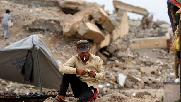 A displaced Iraqi man who fled his home waits outside in Mosul, Iraq.