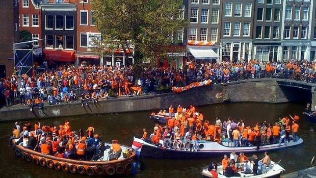 People dressed in orange on the canals of Amsterdam.