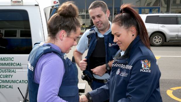 Kate McNaughton, 13, gets suited up for her challenge at the police station with constable Mel Hinga and Chris Maguire.
