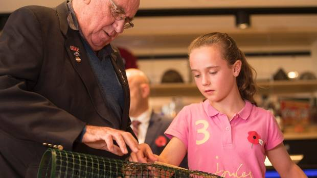 Christchurch RSA president Pete Dawson and Victoria de Costobadie, 11, put together a plastic cage that will be used to ...
