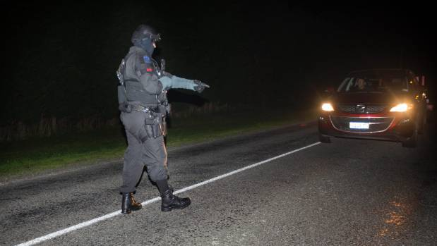 An Armed Offenders Squad member marshals members of the public on Maddisons Rd by Wild Rd near Rolleston.