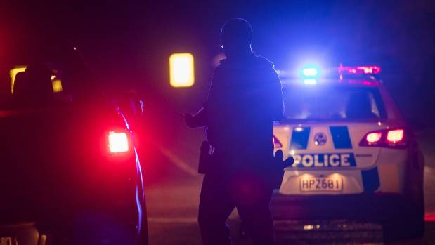 Police talk to a motorist by the intersection of Weedons Ross and Maddisons roads near Rolleston on Wednesday night ...
