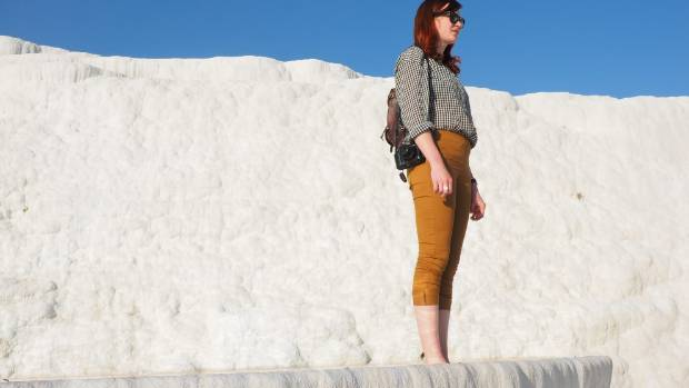 Visit Pamukkale, here a cascade of wide, dazzlingly white limestone terraces flows down a hill.