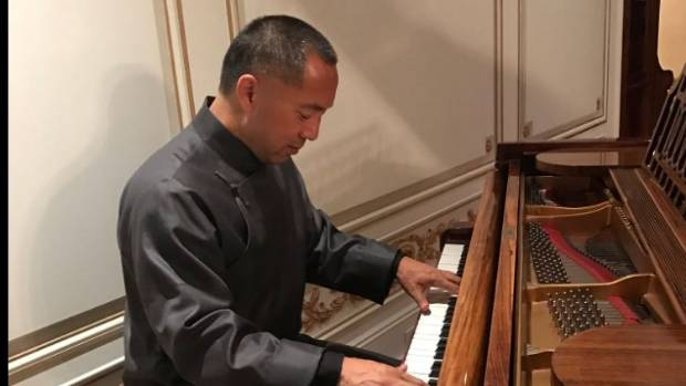 "Guo Wengui plays the piano while an Interpol ""red notice"" has been posted for his arrest."