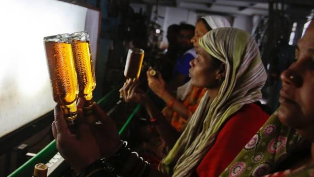 A bottling plant worker checks bottles of Black Power whisky for impurities.