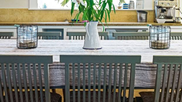 Whitewashed outdoor chairs are used around the dining table.