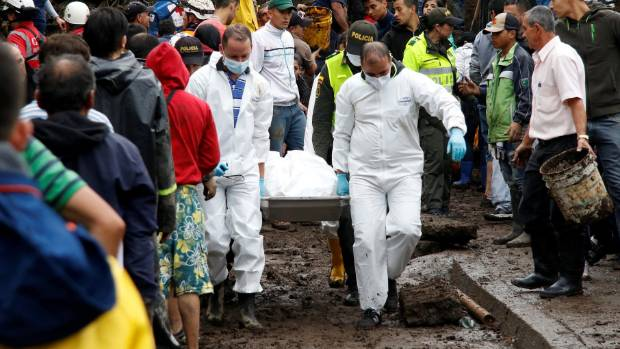 Rescue members recover a body in a house after mudslides in Manizales, Colombia.