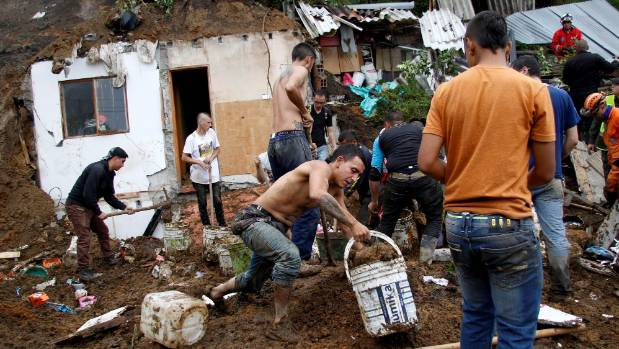 People and rescue agencies look for bodies in a destroyed area.