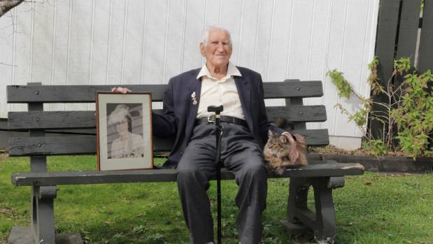 Albert Asher holding a picture of his wife, left, that was taken on their wedding day. The 100-year-old says the army ...