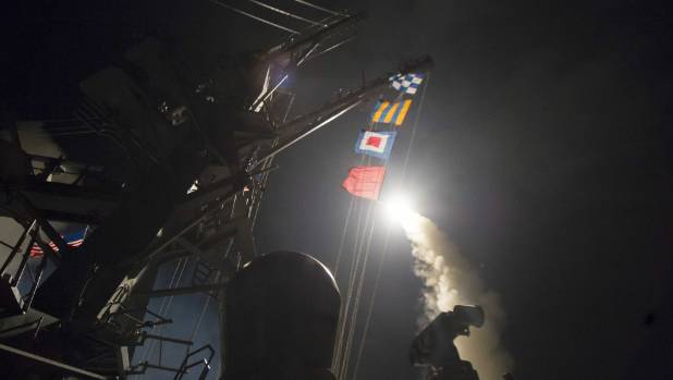 In this handout provided by the US Navy, the guided-missile destroyer USS Ross fires a Tomahawk land attack missile ...