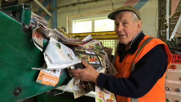 Russell Thwaites loads paper into the bale press.