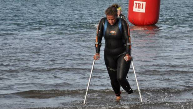 Amputee Lynley Brown leaving the water on crutches following her part in the 2017 Port Of Tauranga Half Ironman.