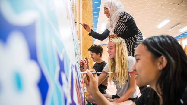 Pictured from top Fatima Azizullah, Megan Pochin, Olive Derecourt, and Mu Pli Toe work on a multicultural mural with a ...