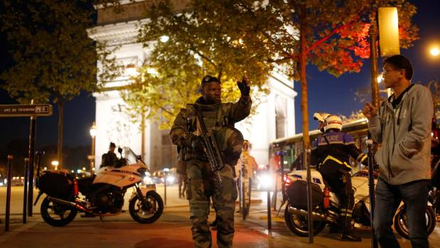 An armed soldier secures a side road near the Champs Elysees Avenue after two policemen were killed and another wounded ...