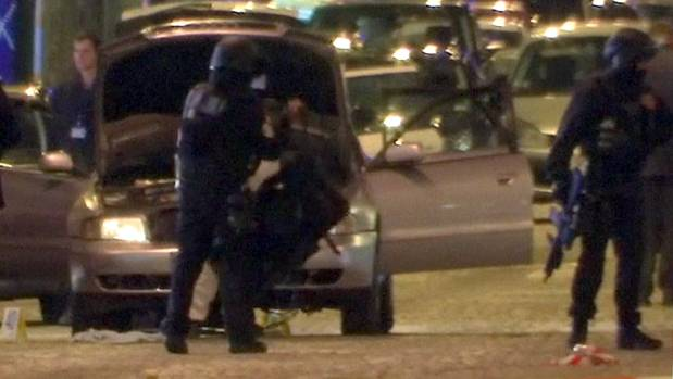 A still image from video footage shows police standing near the car used by the attacker on the Champs Elysees.