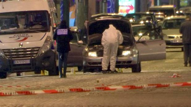 Police inspect the car believed to be used in the attack in central Paris.