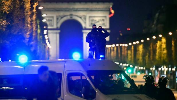 French police officers look through binoculars as others secure the area after a gunman opened fire on Champs Elysees.
