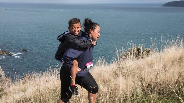 Porirua Grand Traverse, fun run. Maria Ono gives her 6 year old Jacob Meavao an easy ride up Whitirea Summit.