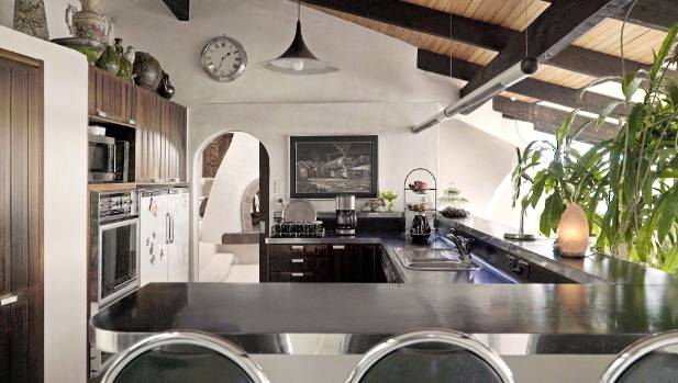 The kitchen is enclosed by a u-shaped island, and tucked beneath the sloping ceiling.