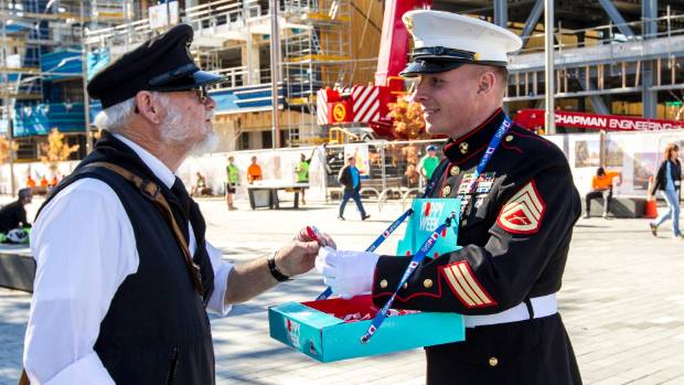 Staff Sergeant Geoffrey Halterman hands a poppy to tram driver Larry Day.