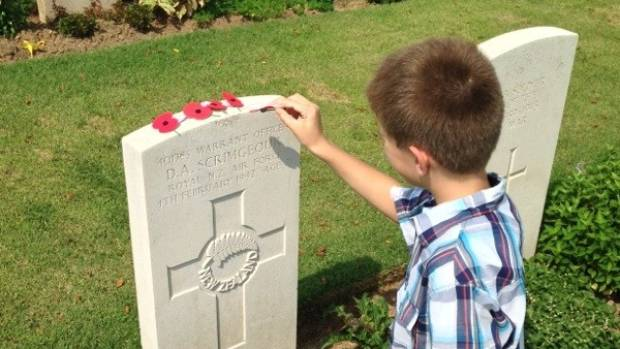 Lukas Oakley places poppies on the grave of Royal New Zealand Air Force warrant officer Denis Scrimgeour on Singapore's ...