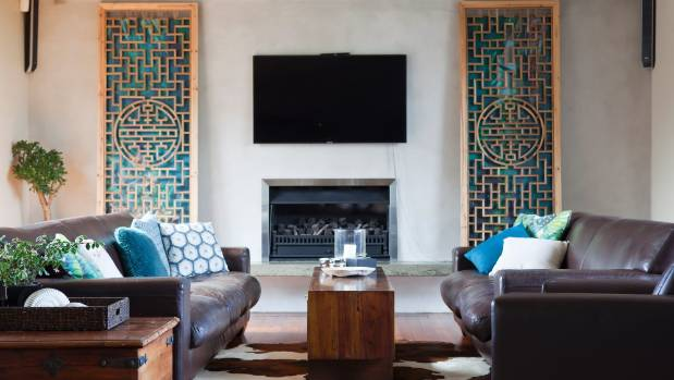 The Asian panels and wall-mounted TV centred above the fire create pleasing symmetry in this space.