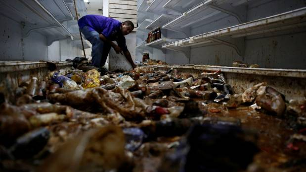 A worker looks for valuables among the damaged goods in a supermarket, after it was looted in Caracas, Venezuela.