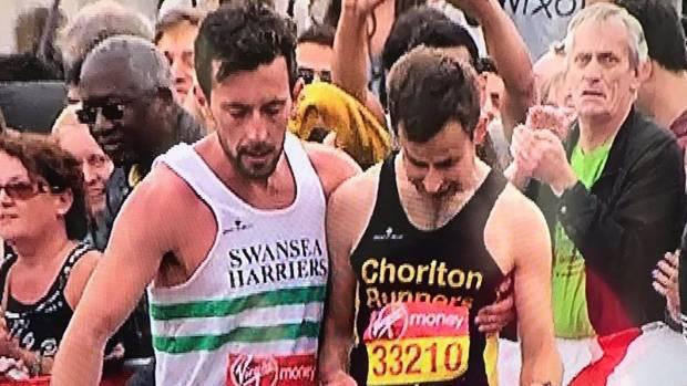 London Marathon runner carried over line by fellow runner