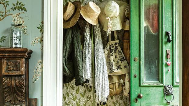 Hats hang on original hall hooks in this country villa.