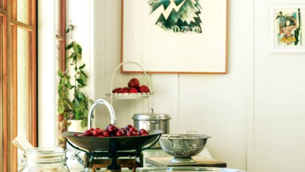 A cottage kitchen is warm and welcoming. Here old scales, which weigh plums for homemade jam, are displayed with a ...