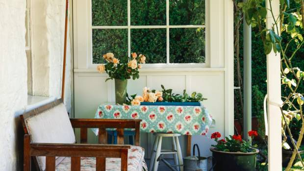 The porch is a quintessential part of the country cottage: here, on-theme decor includes an old watering can, oilcloth ...