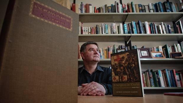 Glyn Harper sits under a shelf loaded with war stories.