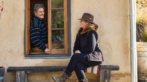 Baz leans out the window to talk to Kate, who sits on a bench made of old totara fence posts.