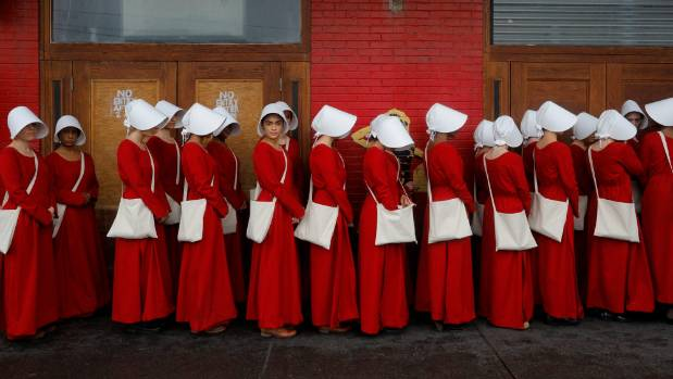Women dressed as handmaids at a promotional event for The Handmaid's Tale.