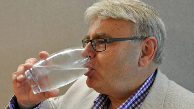 Lower Hutt Mayor Ray Wallace shows the city's treated drinking water is safe to drink earlier this year.
