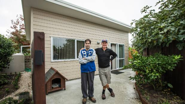 David Barnes, right, with his son Samuel Barnes who needs medical care, pictured with the dwelling David built for him ...
