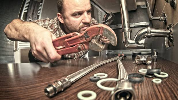 A plumber installs flexible braided hoses.